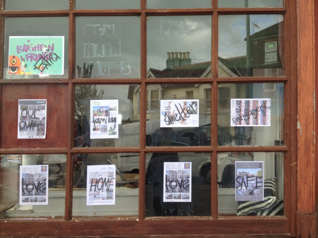An estate agents window displaying images of housing to let with messages of support and solidarity written across them.
